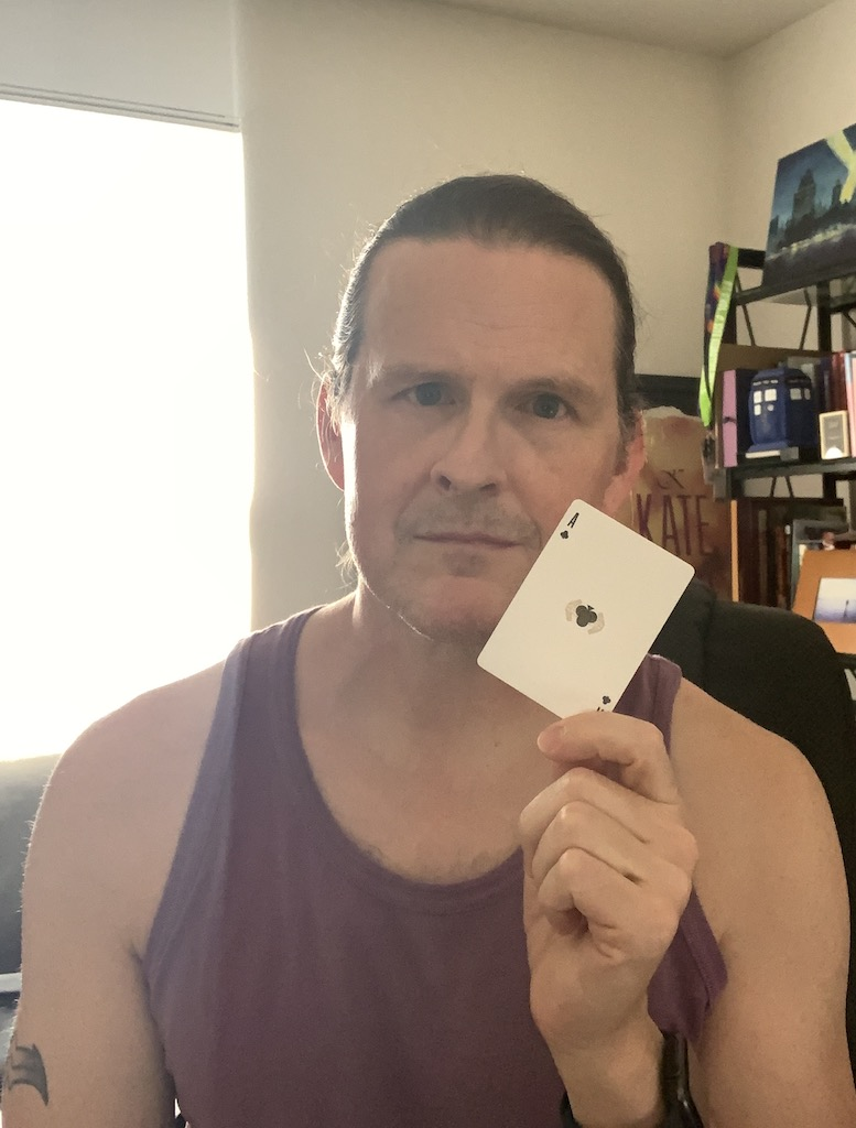 Photo of white male (me) holding a playing card, specifically the ace of clubs.