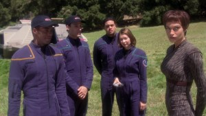 Several Starfleet officers stand on a planet in their uniforms.