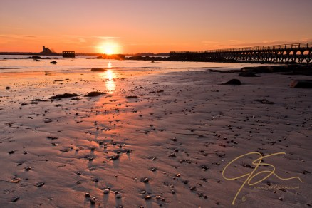 as the sun dips towards the horizon, it casts its golden glow across the wide expanse of sand left exposed by the receding tide.