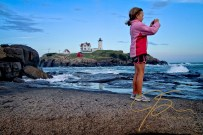 """With the Cape Neddick, aka """"Nubble"""" lighthouse in the background over the rough windswept sea, a young girl dressed in shorts and a pink fleece jacket, stands on the rocks and takes a photograph with her iPhone. Blonde hair pulled back in a ponytail without a care in the world."""