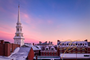 The bright white steeple of the North Church as it towers over the snow covered roof tops of Portsmouth, NH