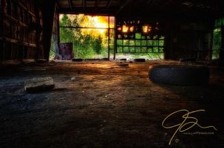 Abandoned garage with sunlight streaming in the broken doors