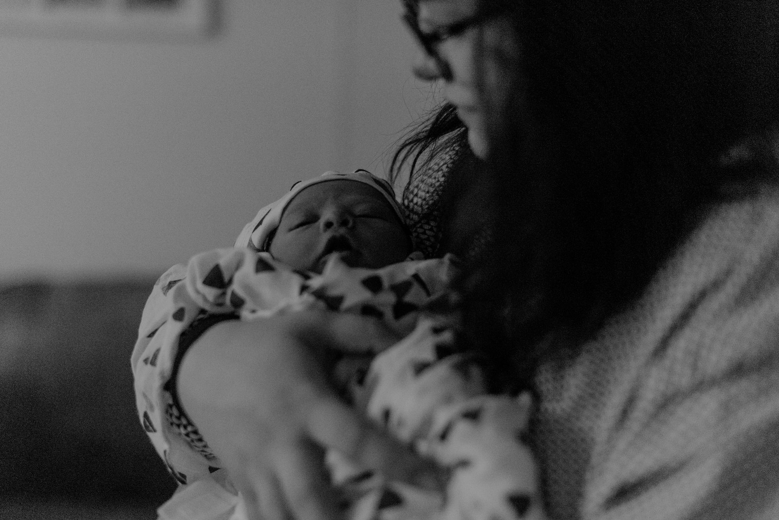 close up black and white image of a new parent holding their baby moments after birth who is swaddled up cozy photo by birth photographer jena lee photographs in golden bc in article about birth photography faq
