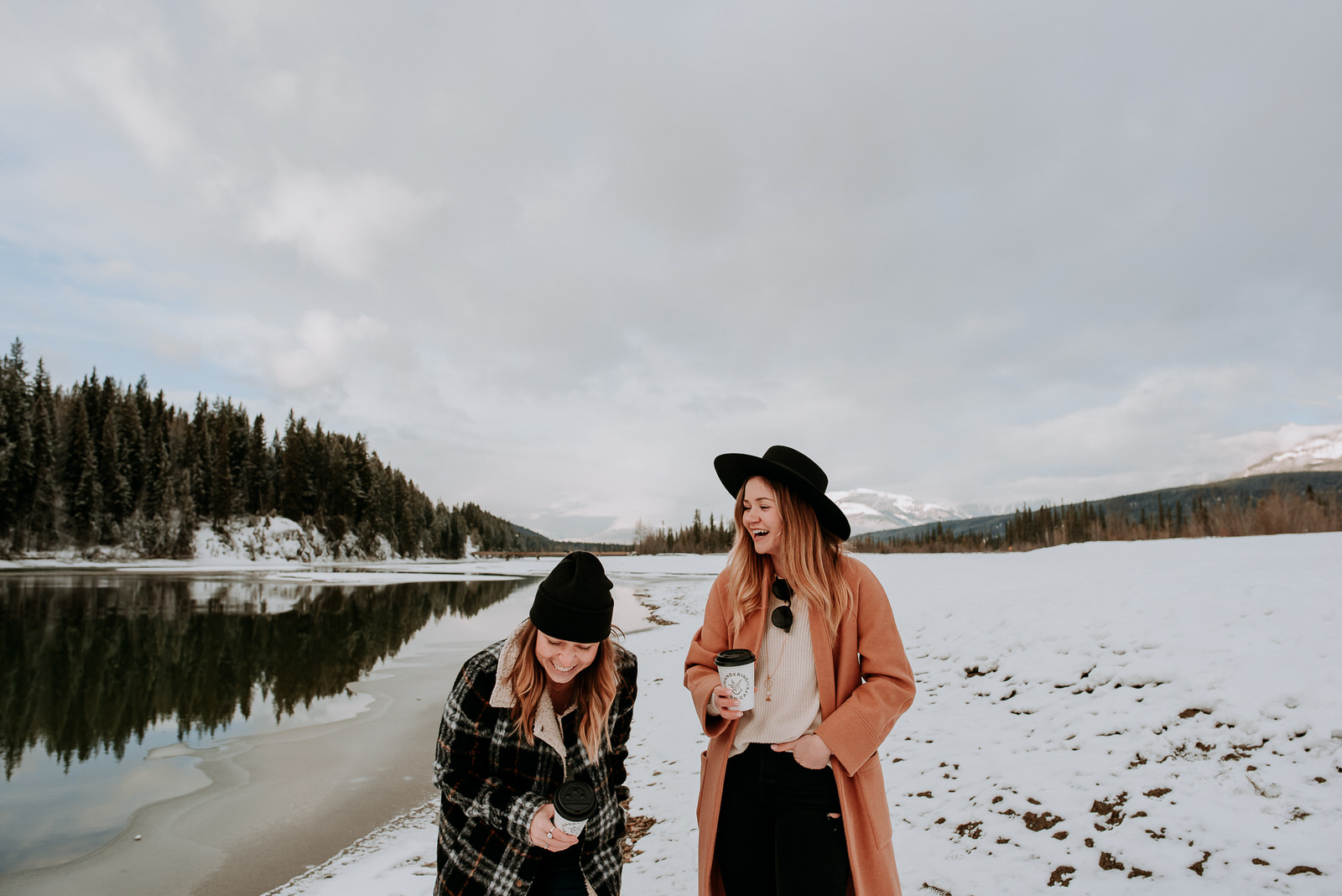 Two women enjoying caffeine free drinks outside by a river during the winter