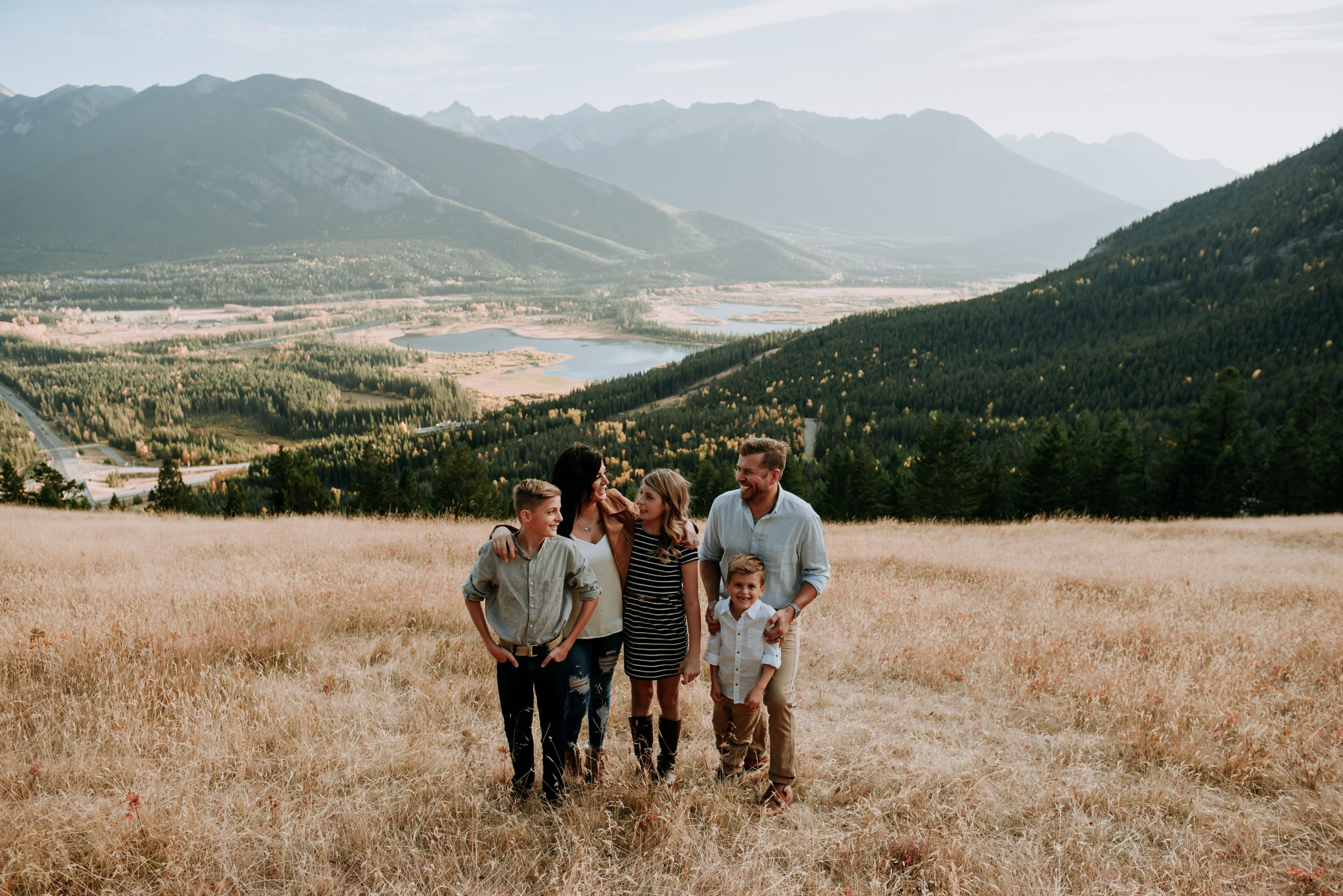 A family stands together candidly in a field with a beautiful rocky mountain background during their family photography session with photographer jena lee photographs
