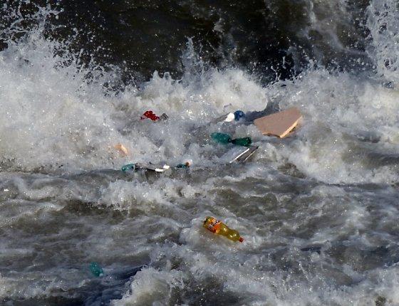 Plastic bottle and Styrofoam caught in tumbling waves of the Tiber River.