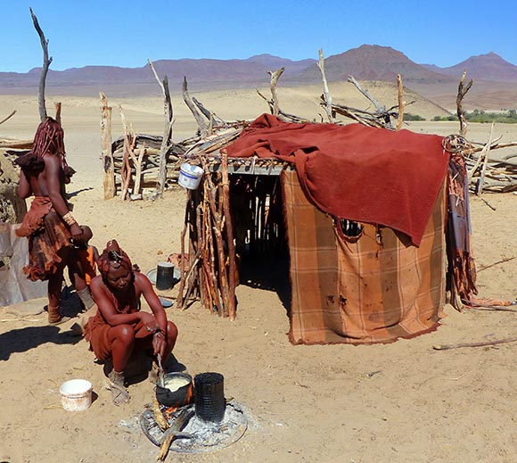 Himba woman cooking cornmeal porridge