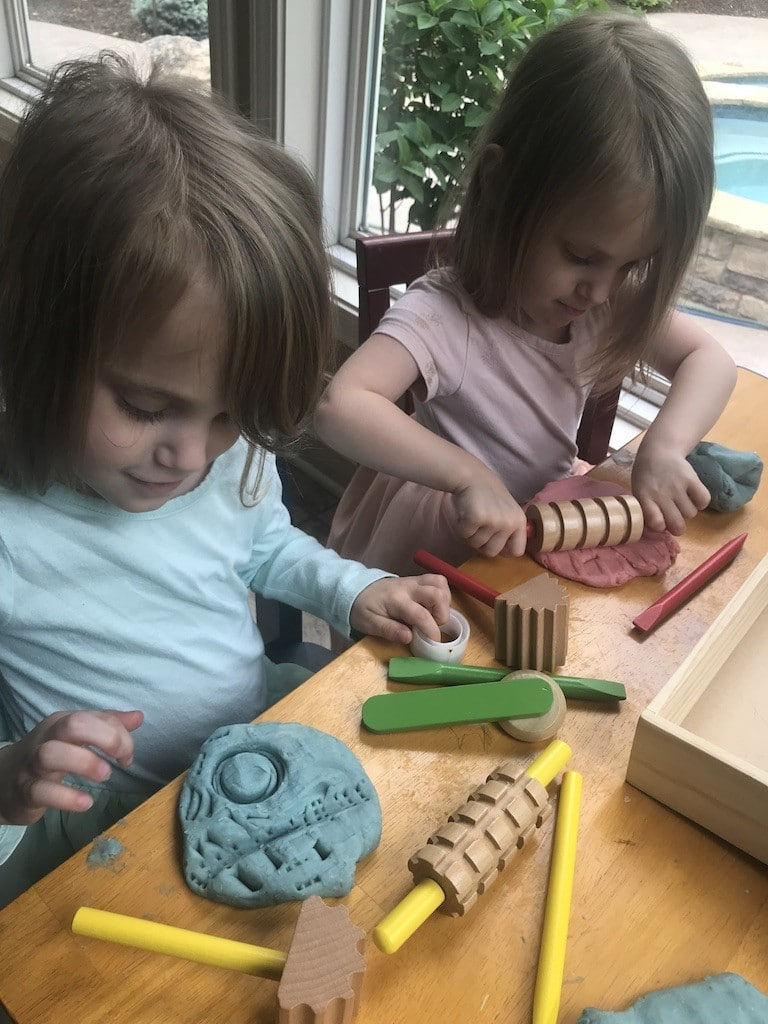 Toddlers playing with play dough and Melissa and Doug tools