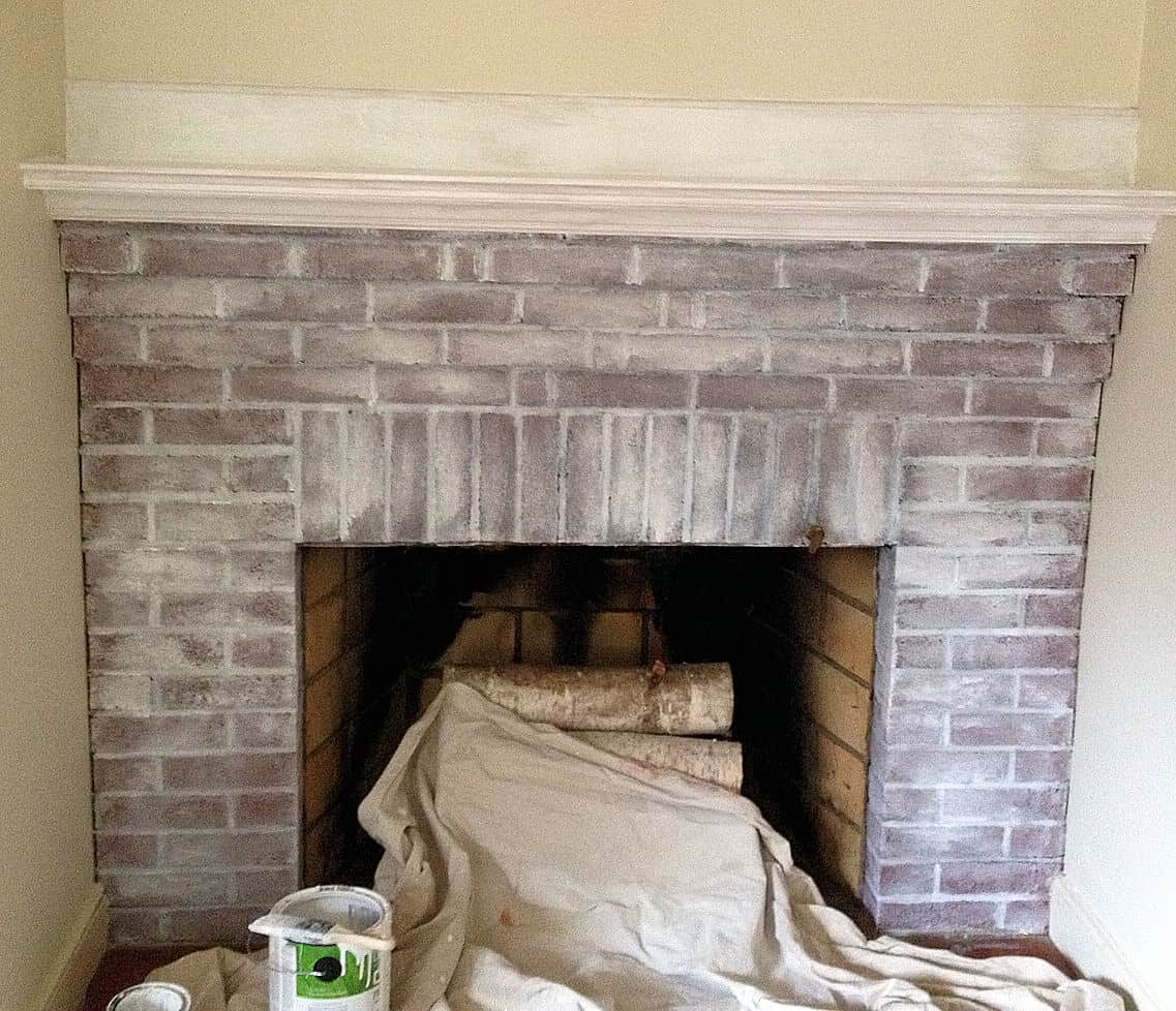 in process shot of red brick fireplace being painted with white wash