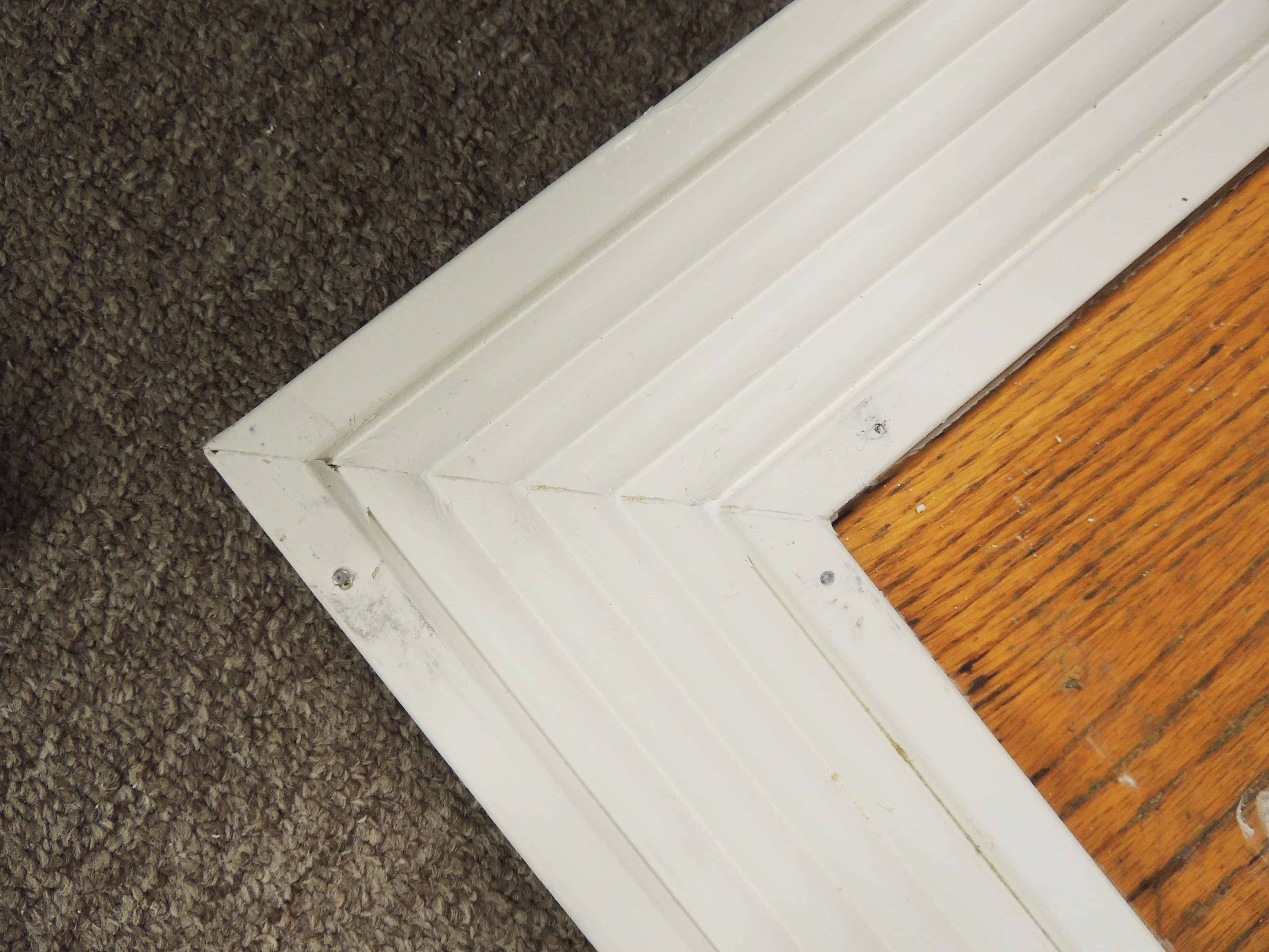 Calking the wooden frame to create a clean finish for the floor-mirror.