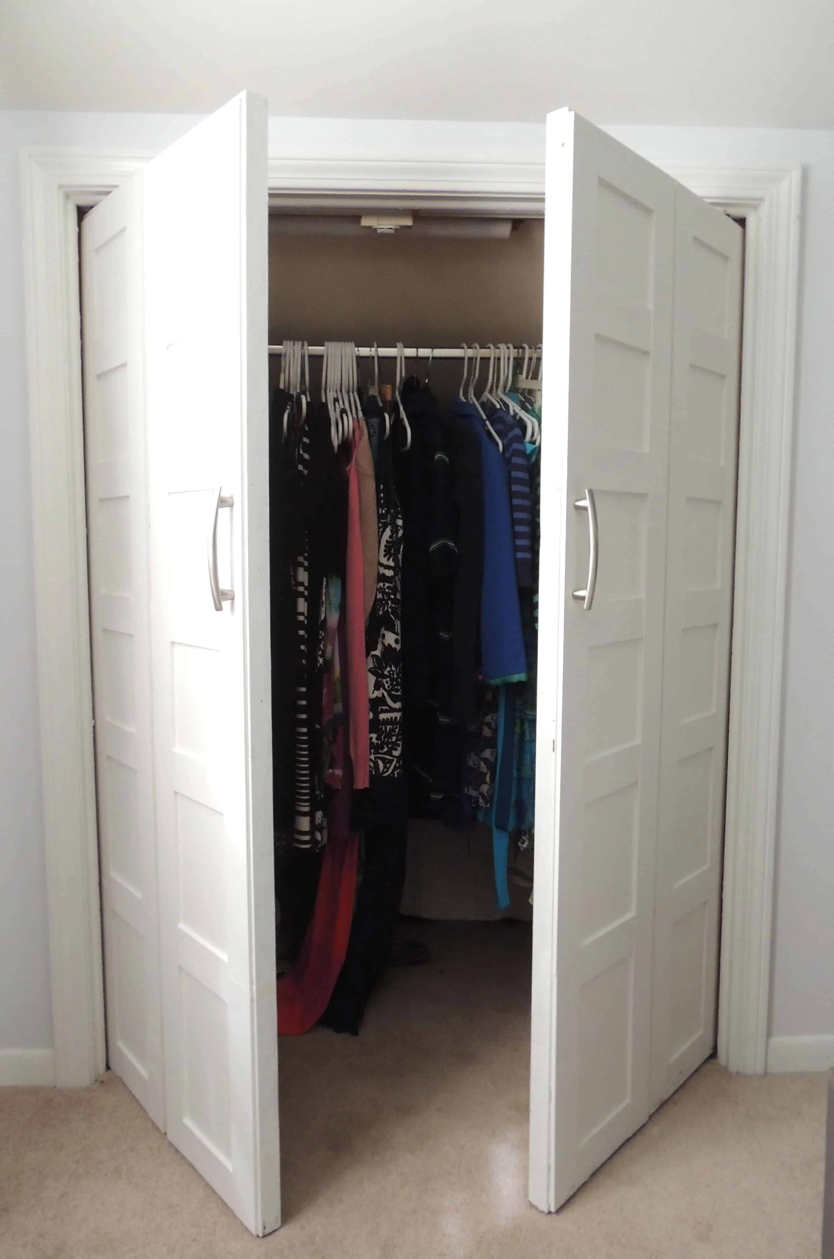 White bifold closet doors, slightly opened, now swinging out instead of folding