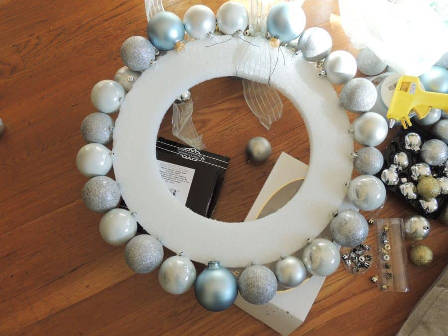 Use hot glue to attach the Christmas ornaments to the wreath frame.