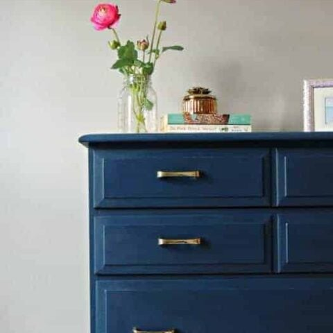 Tall dresser painted in deep blue with silver hardware, with vase of flowers resting on top