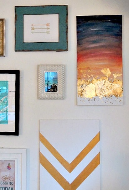 The finished watercolor art now hangs among other artwork and photo frames on wall
