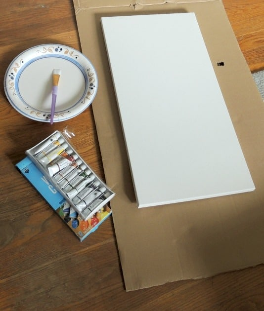 Paint supplies set up on table: watercolor paints, blank canvas resting on cardboard, and paint brush in paper plate