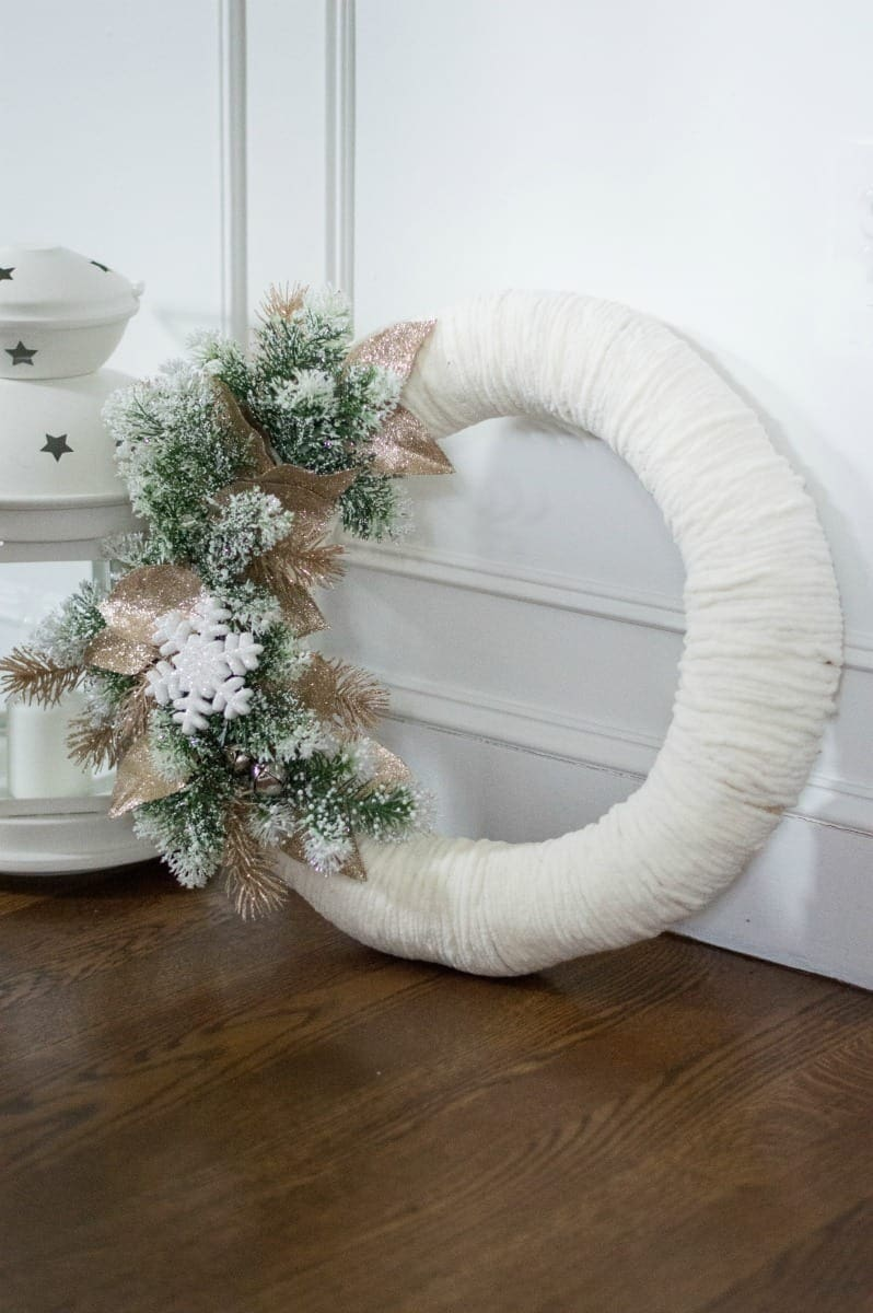 Keep your winter wreath indoors and hang it over your fireplace mantel or by a window