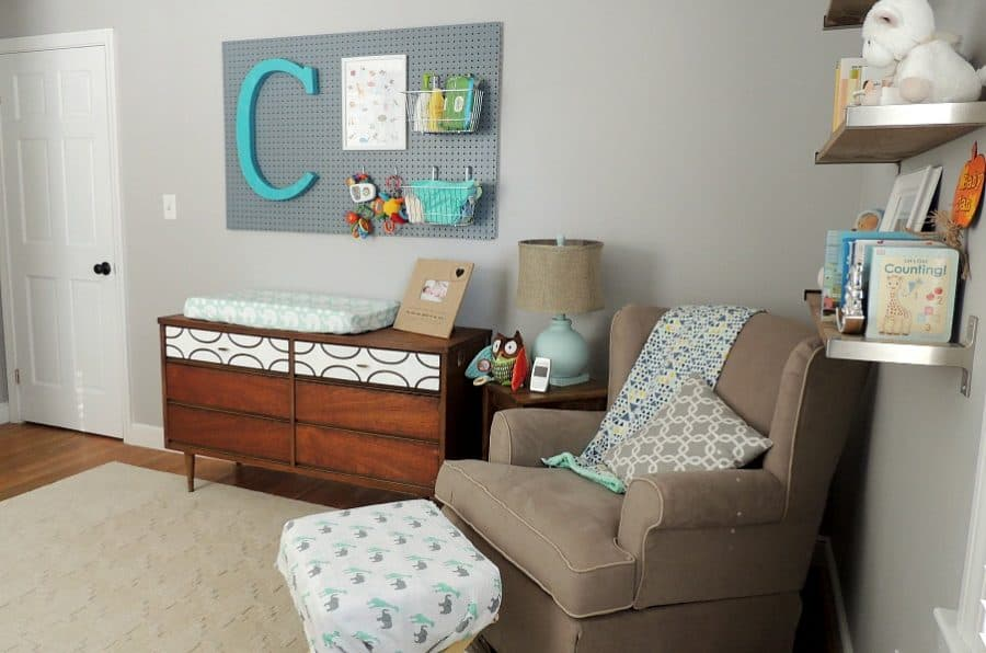 The nursing and sitting area in Cian's baby nursery is a comfy corner with a gray fabric chair