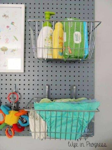 Grey painted wooden pegboard holding wire baskets of baby changing supplies