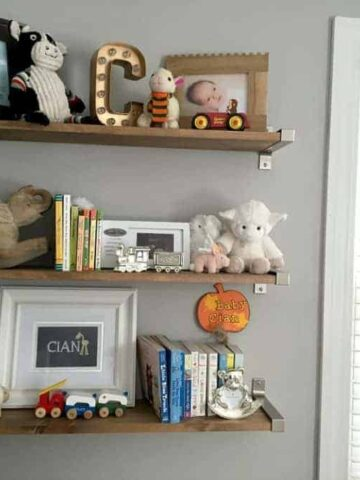 3 brown shelves holding photo frames and various nursery room decor