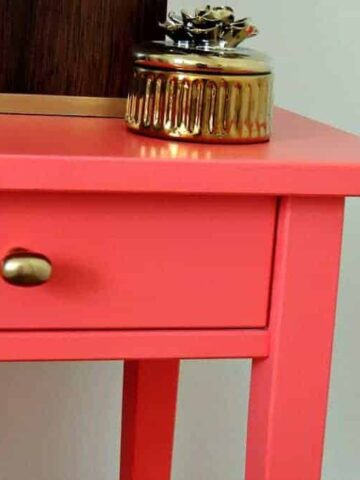 Coral nightstand next to guest room bed, with a wood-tone lamp resting on top