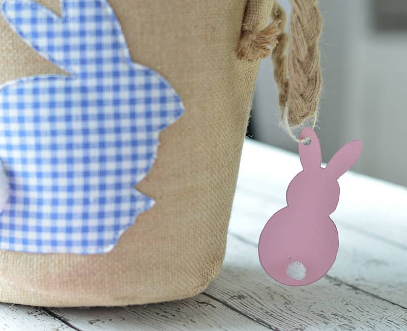 Pink paper Easter bunny hanging from the corner of a canvas Easter basket