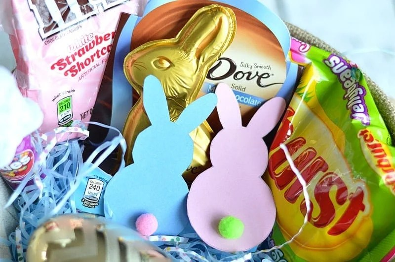 Pink and blue paper Easter bunnies with cute little pom pop tails in a basket filled with candies