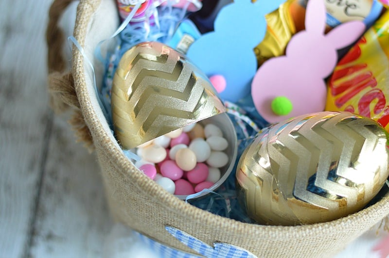 Golden chevron-patterned plastic Easter eggs, filled with pink candies, with paper bunnies nearby in canvas basket