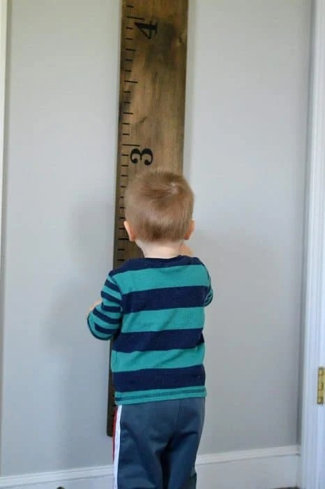 Young boy admiring height measurement on life size growth chart