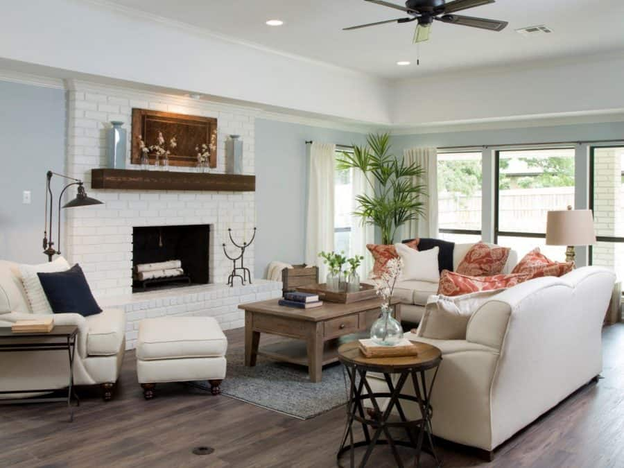 Farmhouse style living room with painted brick fireplace and rustic mantle