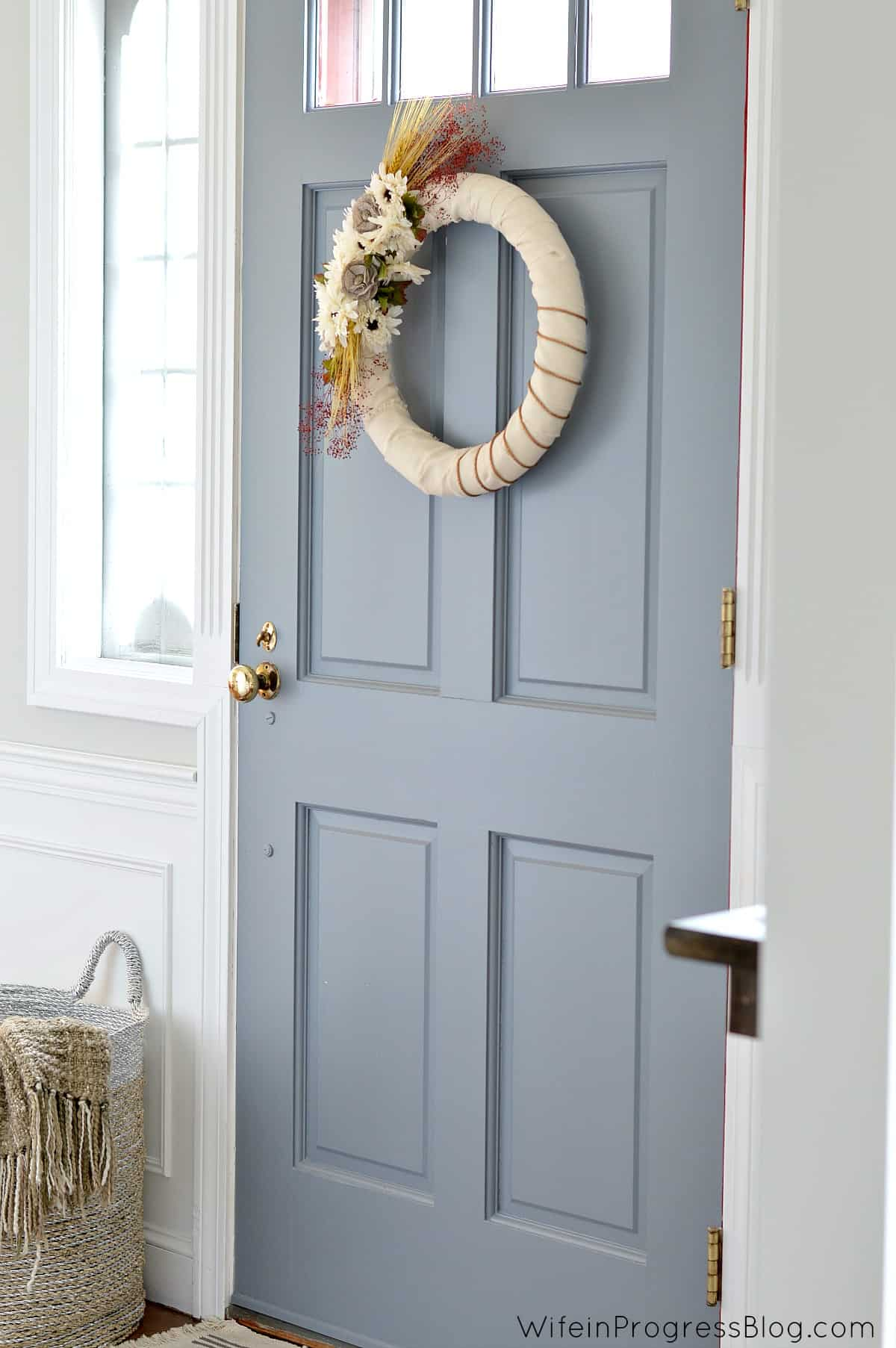DIY fall wreath hanging on a blue door