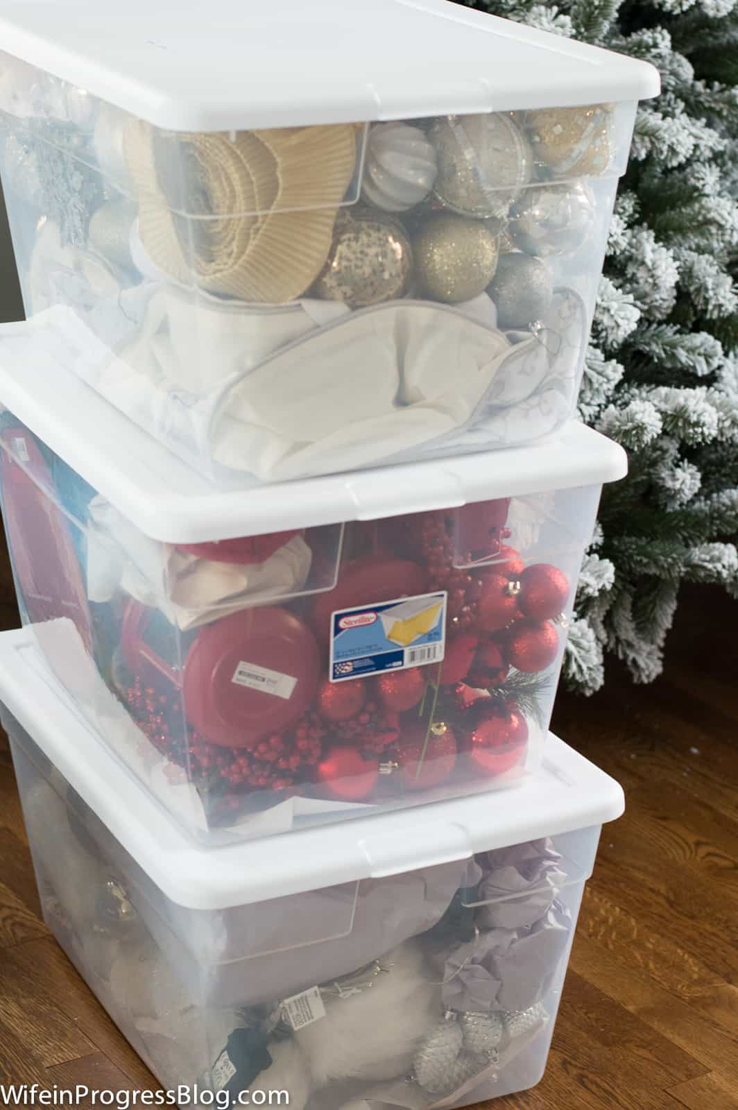 Organize Christmas ornaments by color in clear tote bins