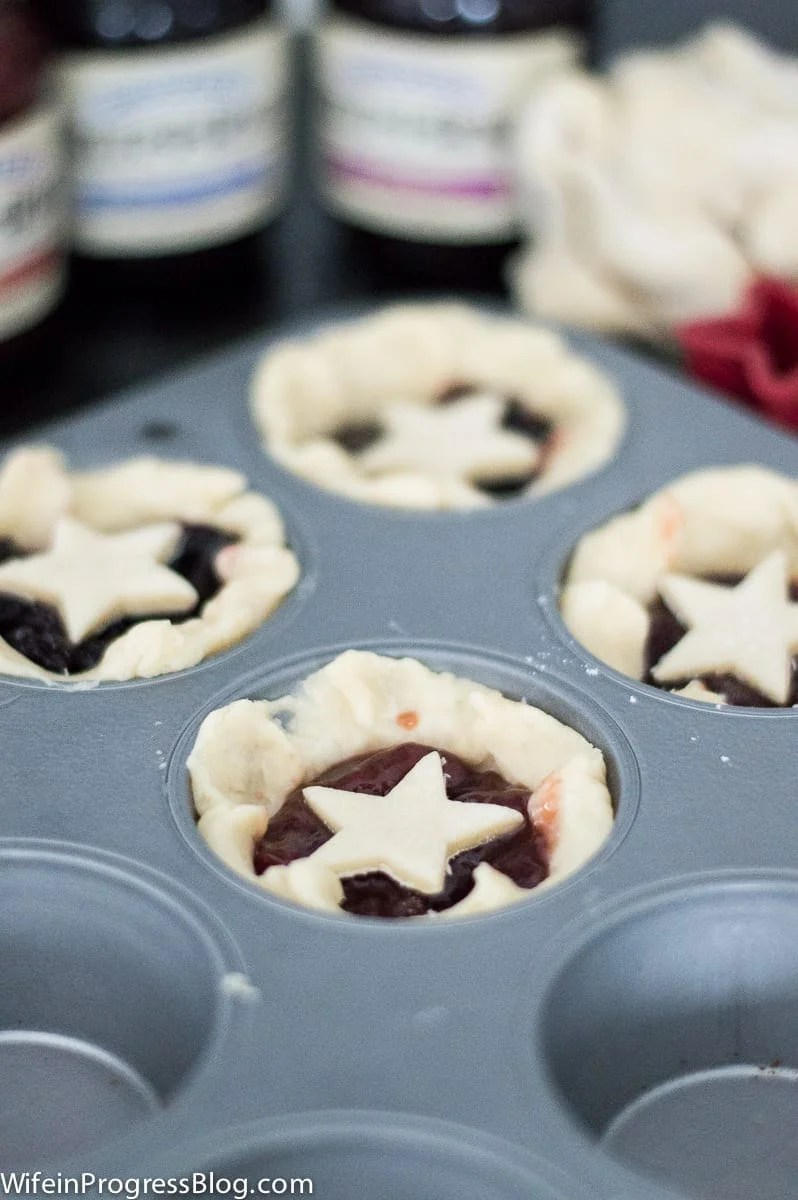 filling the tarts with jam before baking