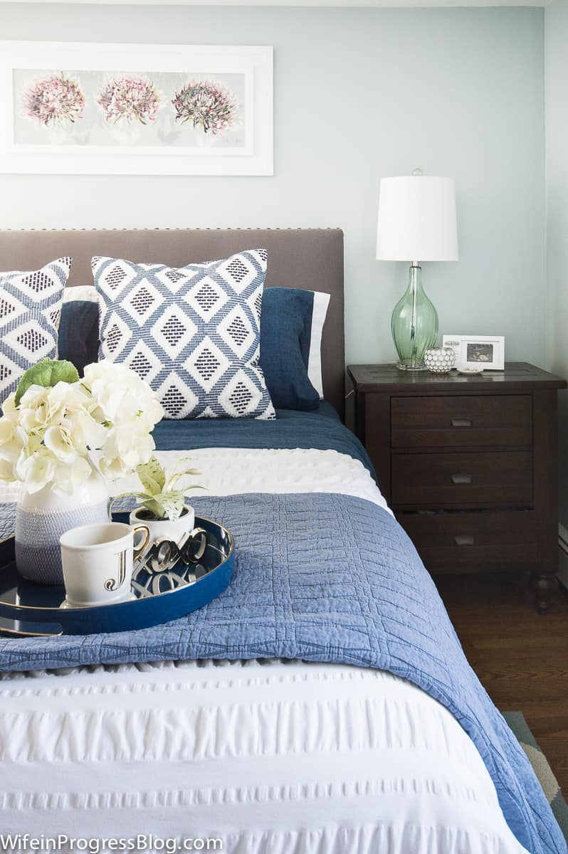 Soft blue bedding and bright flowers give warmth to this winter bedroom refresh