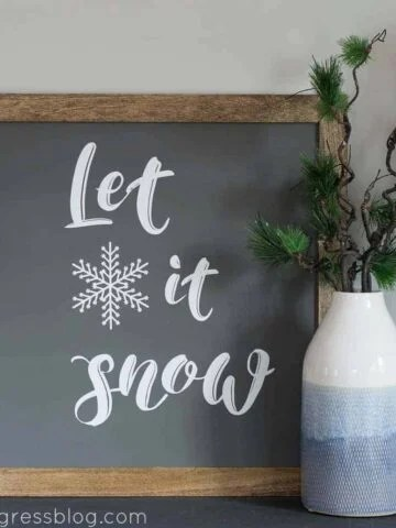 """A square, wood-framed board, painted black, with the words """"Let it snow"""", in white, adjacent to a blue and white vase with greenery"""