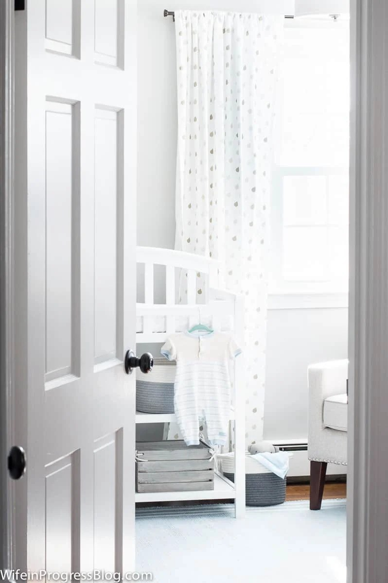 A stunning gray and blue baby boy nursery featuring a reclaimed wood accent wood.