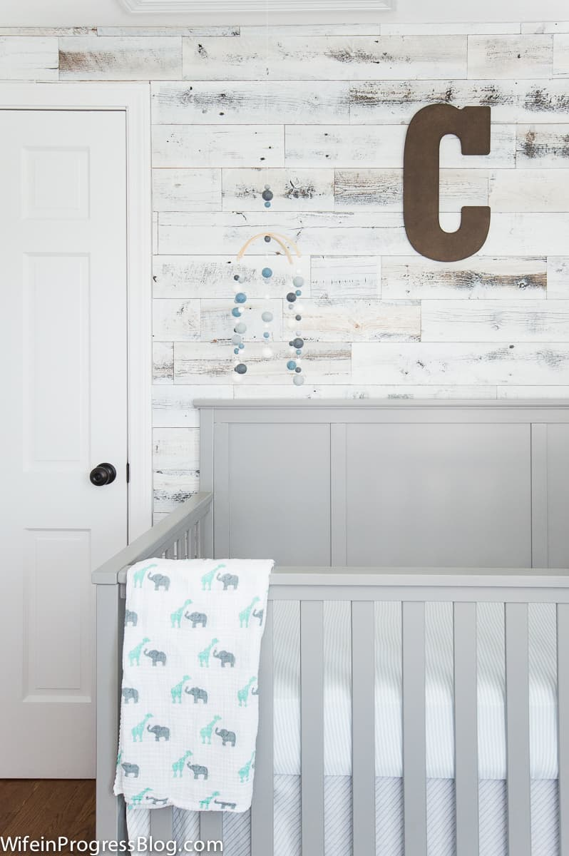 A classic gray and blue baby boy nursery featuring a reclaimed wood accent wood.