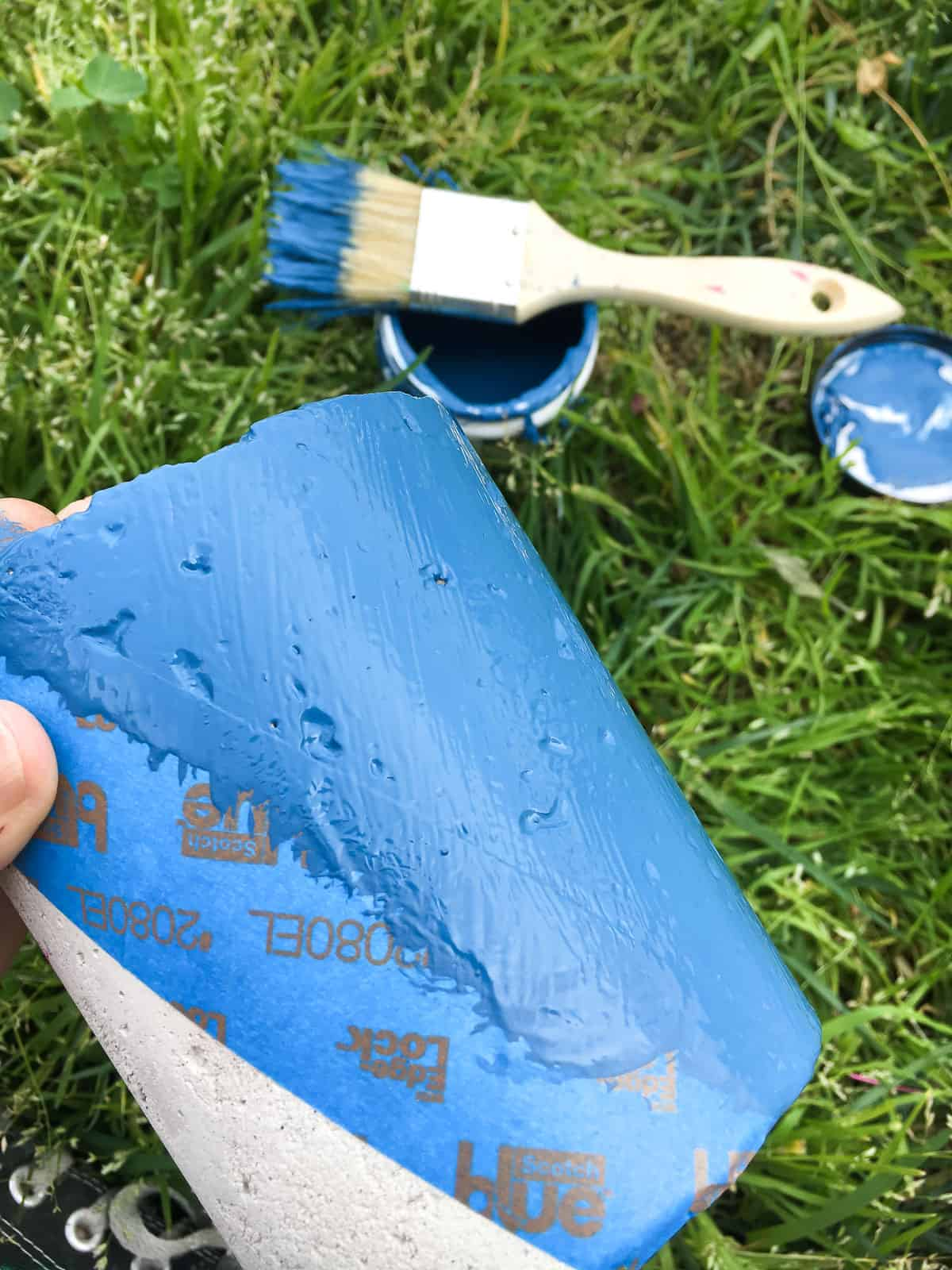 One concrete planter receives a layer of blue paint, at an angle defined by blue painter's tape