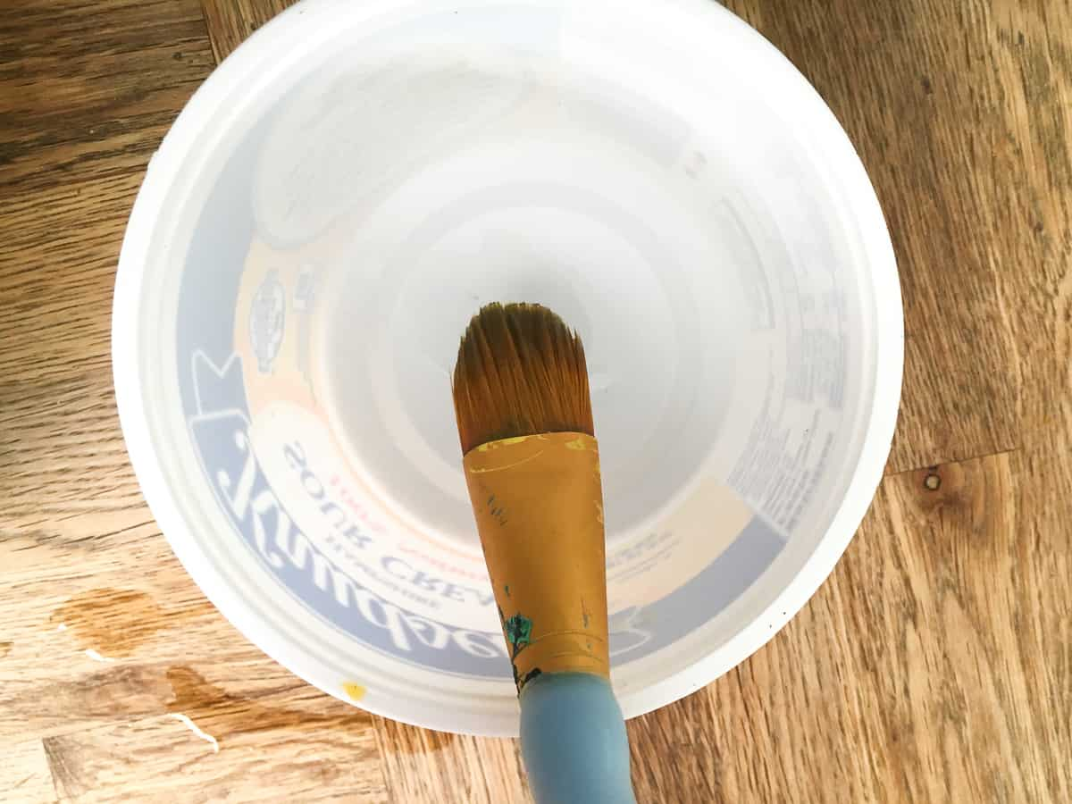Applying oil to the inside of the exterior container with a large paint brush.
