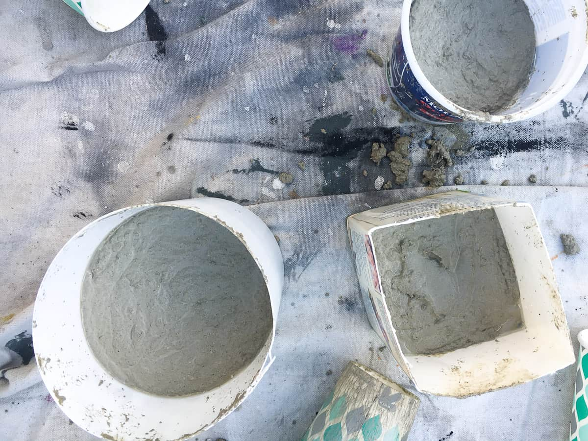 A group of three containers holding the first pour of concrete mix (2 round and 1 square), all resting on a drop cloth.