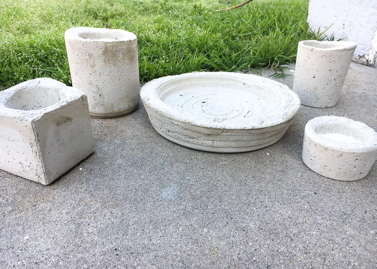 The freshly dried molds, separated from their plastic containers, sitting on a concrete patio, near a grassy area