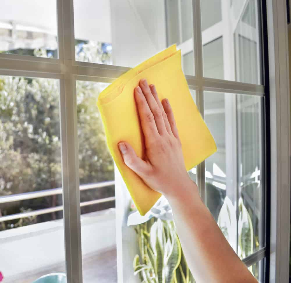 hand wiping clean a window