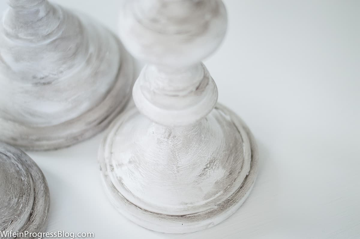 A close-up view of the effects of the antiquing wax on the white painted candles
