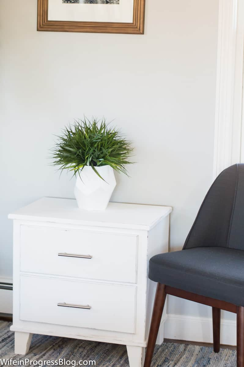 Nightstand, now white and distressed, holding an arrangement of greenery in a white vase, next to a blue accent chair