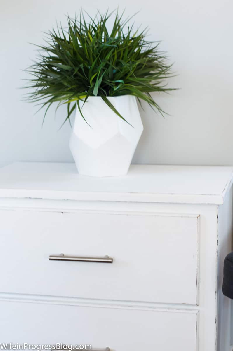 White chalk-painted nightstand with white vase of greenery on top