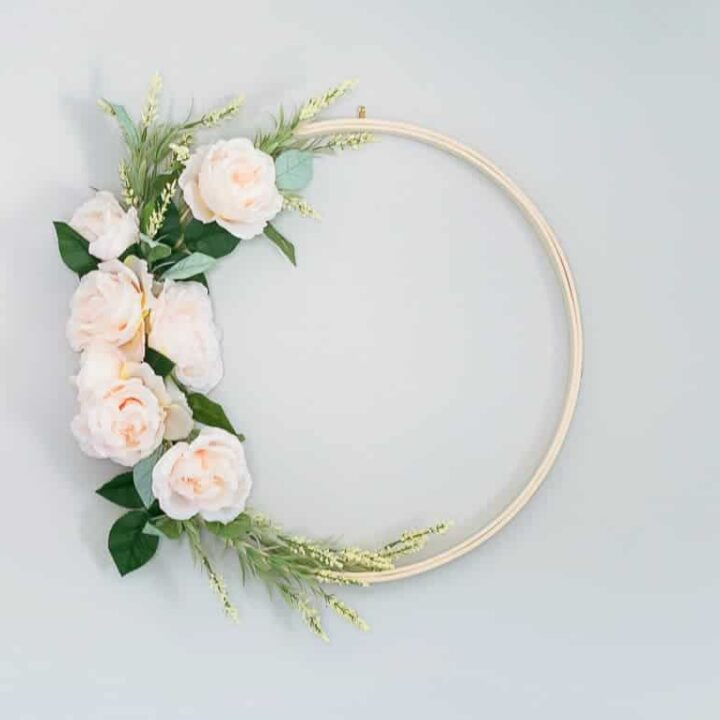 Wreath with an embroidery hoop base, covered on left side with light pink flowers and green sprigs