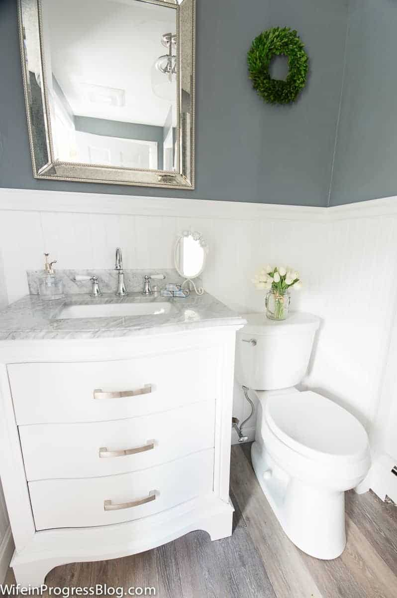 Our budget-friendly master bathroom update included a new vanity, toilet, and new beadboard wall covering