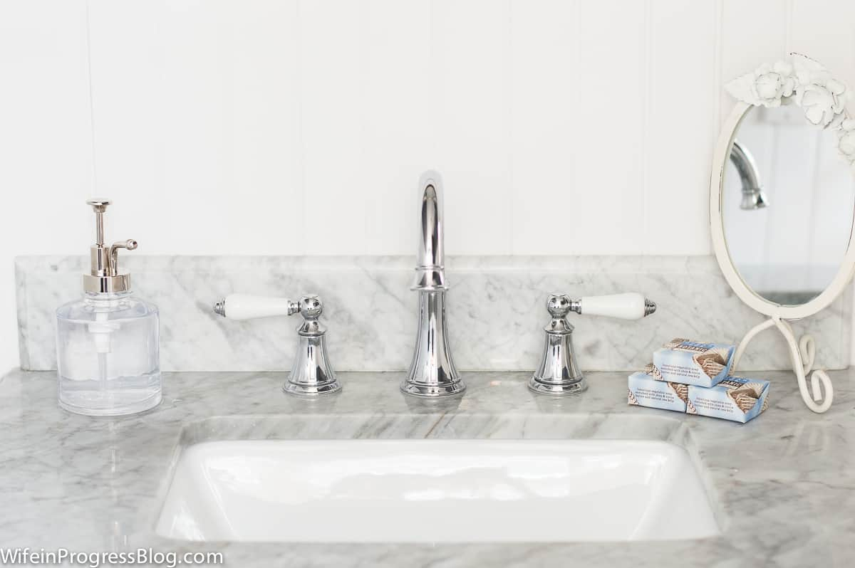 The new bathroom vanity with white marble and chrome hardware is really sleek and clean