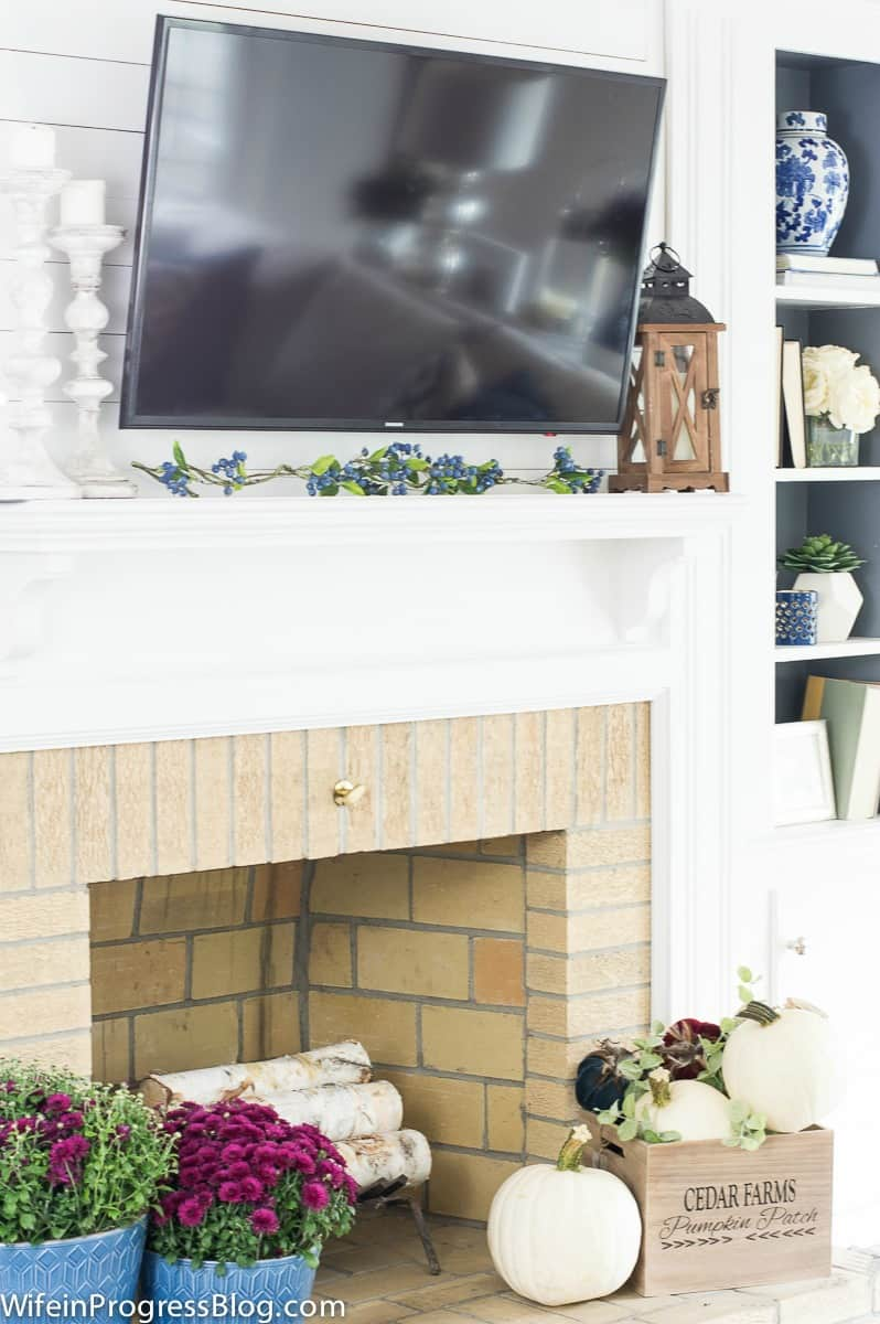 Decorating a fireplace with mums and pumpkins for fall