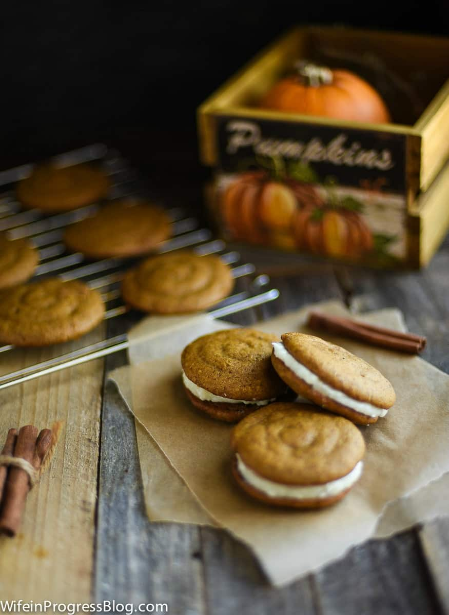 Pumpkin whoopie pies with cream cheese filling with more resting on a wire rack