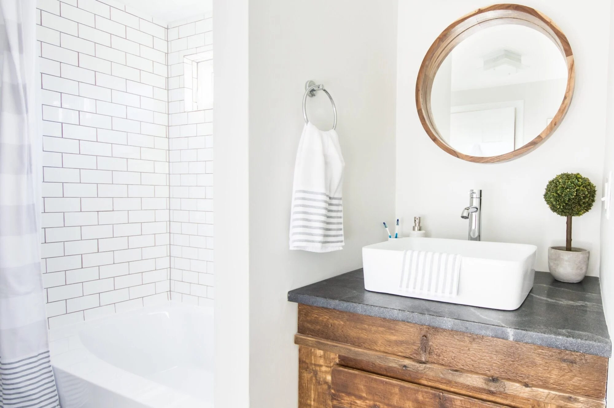Updated farmhouse bathroom with white subway tiles near bathtub and a rustic sink set in custom wood vanity